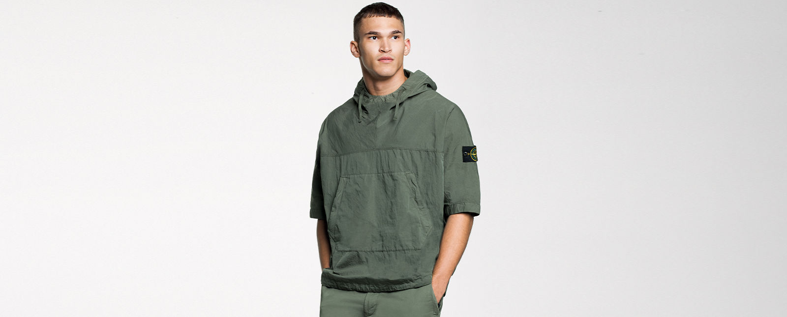 Model wearing a green short sleeved hooded overshirt with central pouch pocket and the Stone Island badge on the left sleeve.