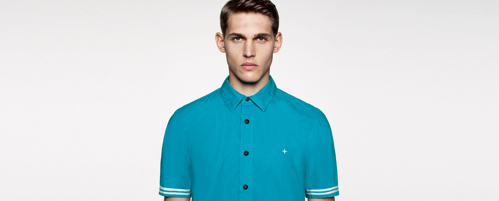 Portrait shot of a model wearing a blue short sleeved shirt with black buttons, white stripe details on the sleeves, and a white Stone Island stella on the chest.