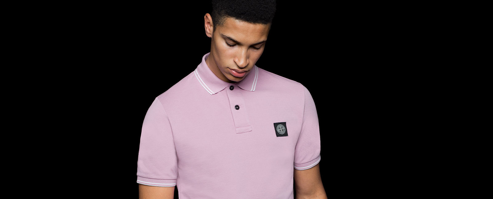 Model wearing a light pink short sleeved polo shirt with white stripes on the cuffs and collar, black buttons, and the Stone Island patch on the chest.