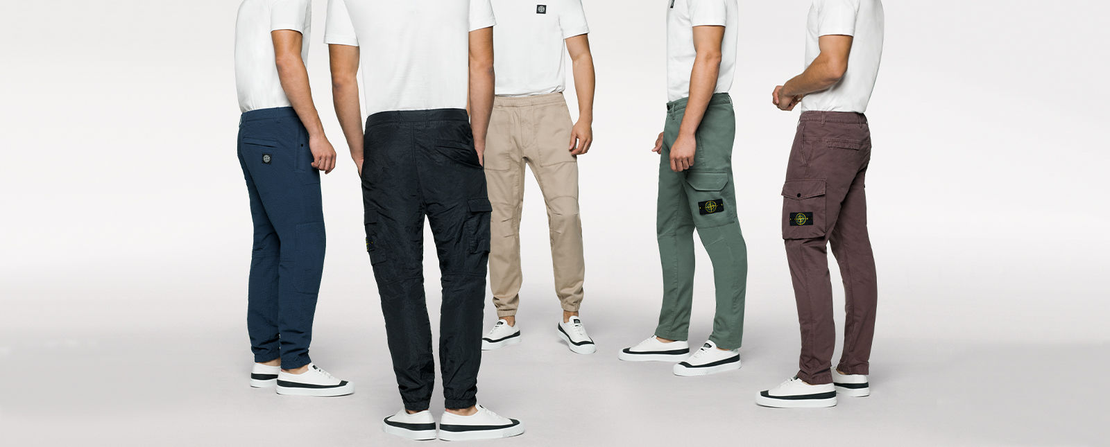 Five models standing in a semi circle and wearing white t shirts and cargo pants with pockets in black, dark blue, tan, green, and maroon.