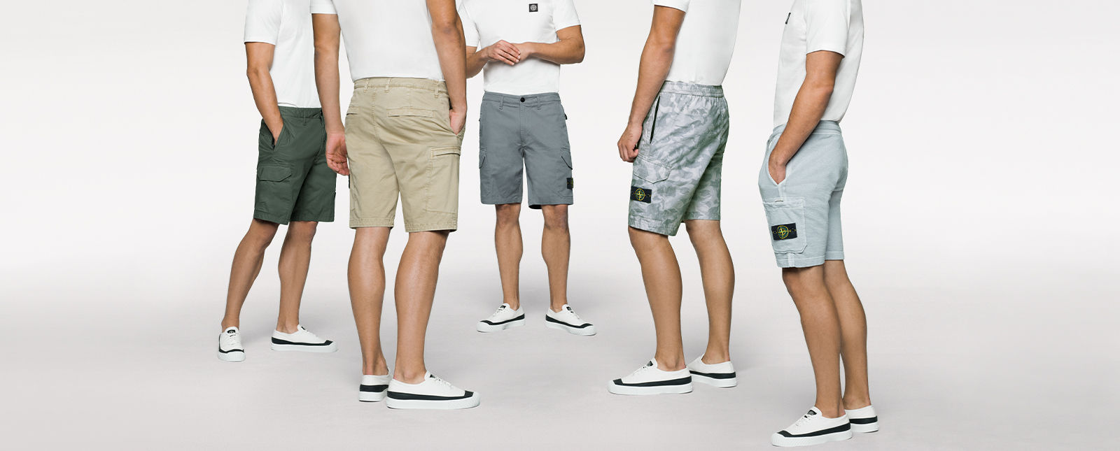 Five models standing in a semi circle and wearing Bermuda shorts with pockets in khaki, green, solid dark gray, patterned gray, and light gray.