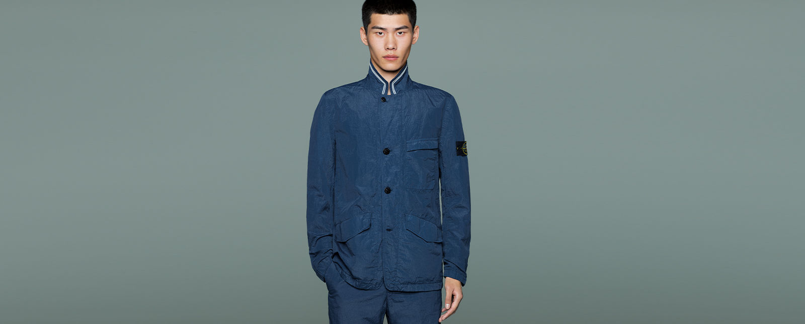 Model wearing dark blue jacket with Mandarin collar with white striped trim, black buttons down the front, chest pocket, side pockets, together with matching pants.