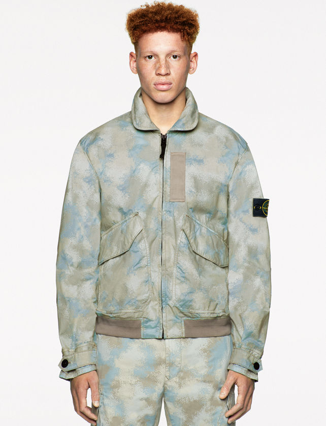 Model wearing a light blue and tan camouflage print collared jacket with tan accents, flap pockets, buttoned sleeve cuffs, and matching pants