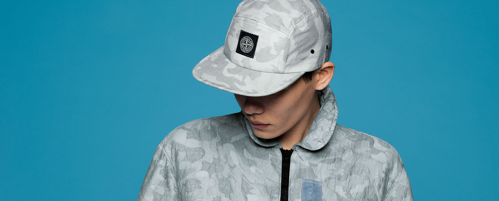 Model wearing light gray camouflage print baseball cap with the Stone Island patch on the front and matching jacket with black zipper closure.