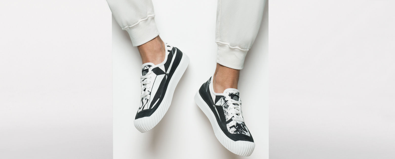Black and white abstract printed sneakers with thick white rubber sole and white laces on the feet of a model wearing white sweatpants.