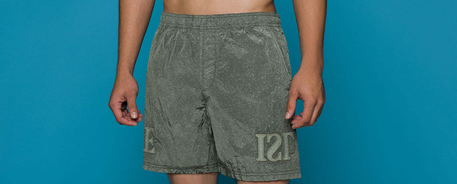 Model wearing speckled green swim shorts with elastic waistband, side pockets, and lettering on the lower leg.