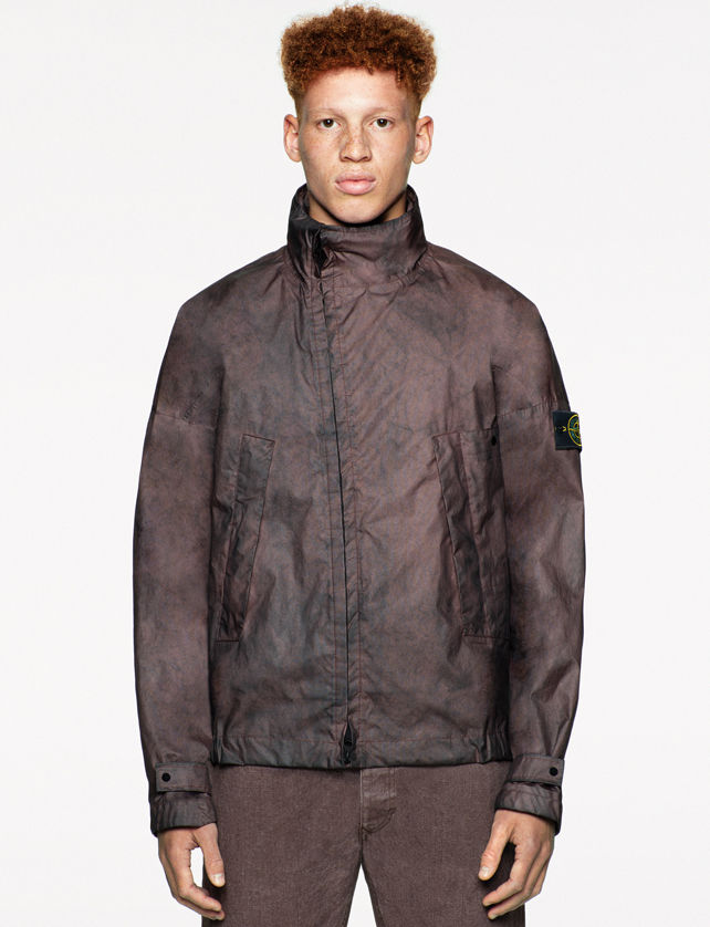 Model wearing a jacket with a black and brown spray paint effect, high collar, zipper down the front, Stone Island badge on the left sleeve