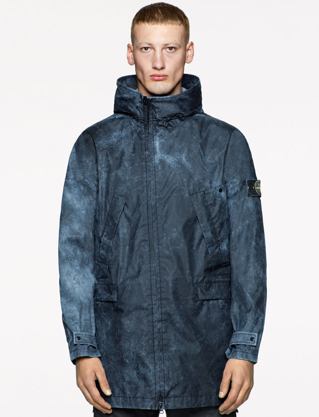 Model wearing a jacket with a black and blue spray paint effect, high collar, zipper down the front, Stone Island badge on the left sleeve and buttoned cuffs