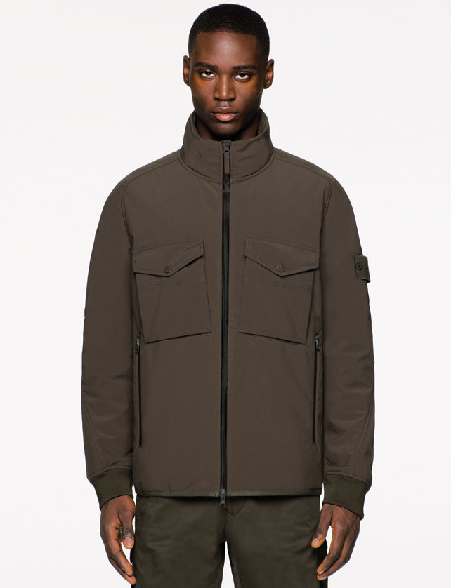 Model wearing a dark brown jacket with black zipper closure, high collar, flap pockets on the chest, together with matching pants