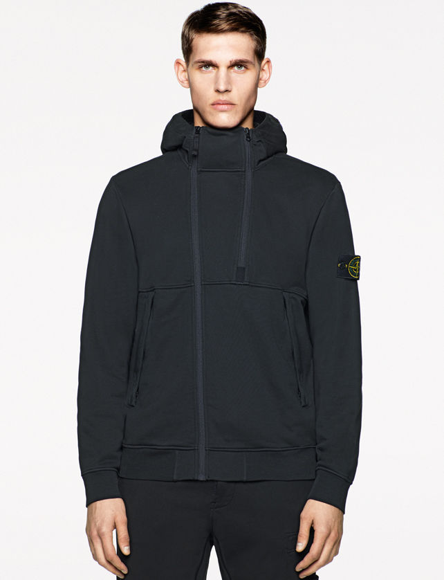 Model wearing a black sweater jacket with a stand collar, dual zipper closure, and Stone Island badge on the left arm