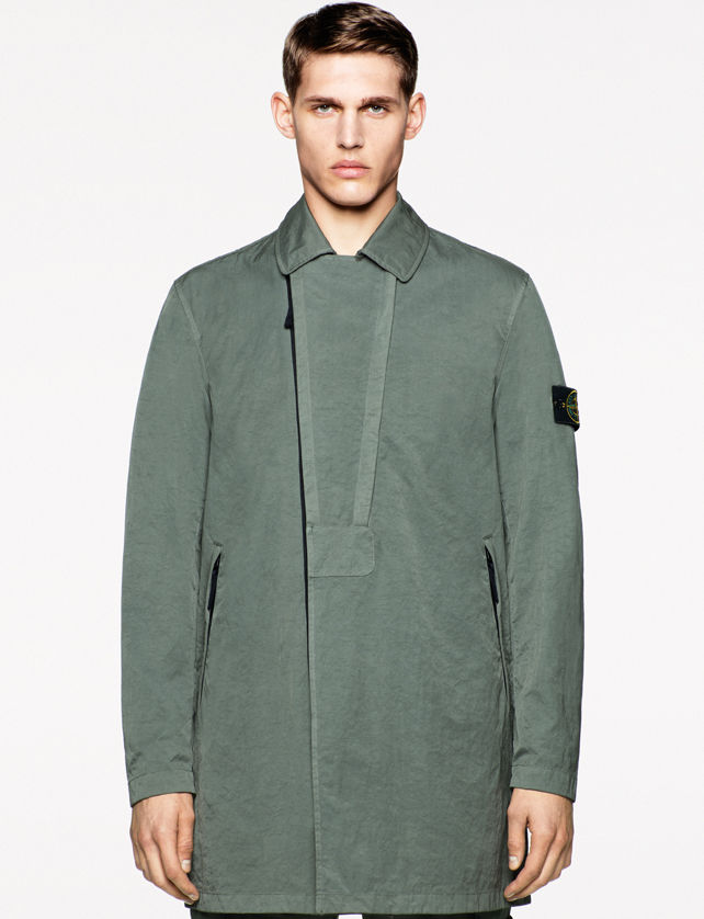 Model wearing a mid length green jacket with black asymmetrical zipper closure, collar, and Stone Island badge on the left arm