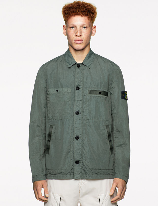 Model wearing a green shirt jacket with collar, black button closure, buttoned chest pockets, side pockets, and white pants