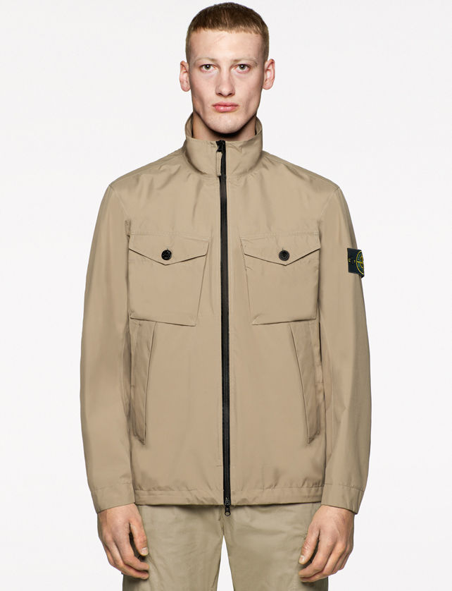 Model wearing a structured tan jacket with black zipper down the front, stand collar, buttoned chest pockets, and Stone Island logo badge on the left sleeve