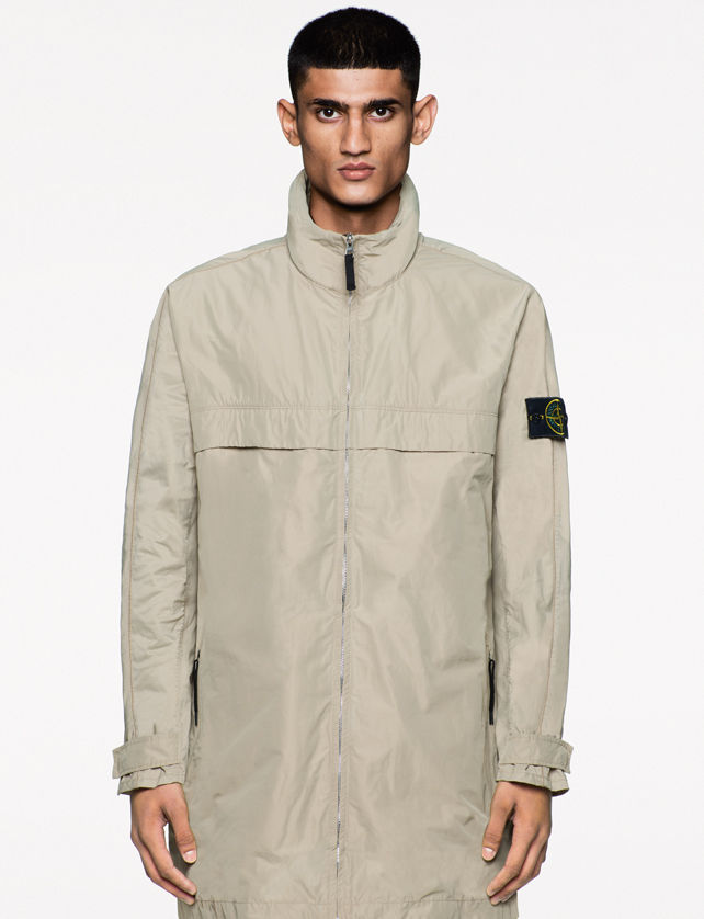 Model wearing a mid length light khaki zip up jacket with black zipper tab, high collar, and Stone Island badge on left arm