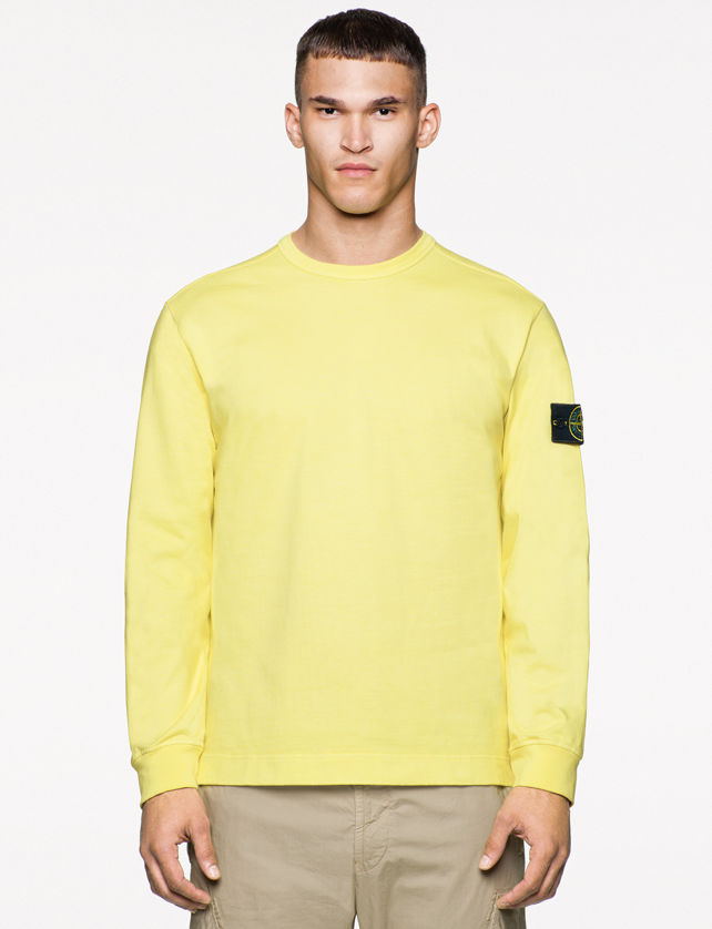 Model wearing a light yellow sweater with Stone Island badge on the left arm and tan pants