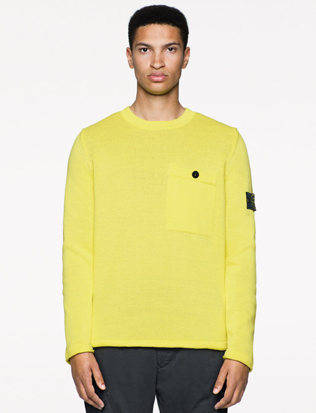Model wearing a light yellow sweater with chest flap pocket with a black button on the left and Stone Island badge on the left arm