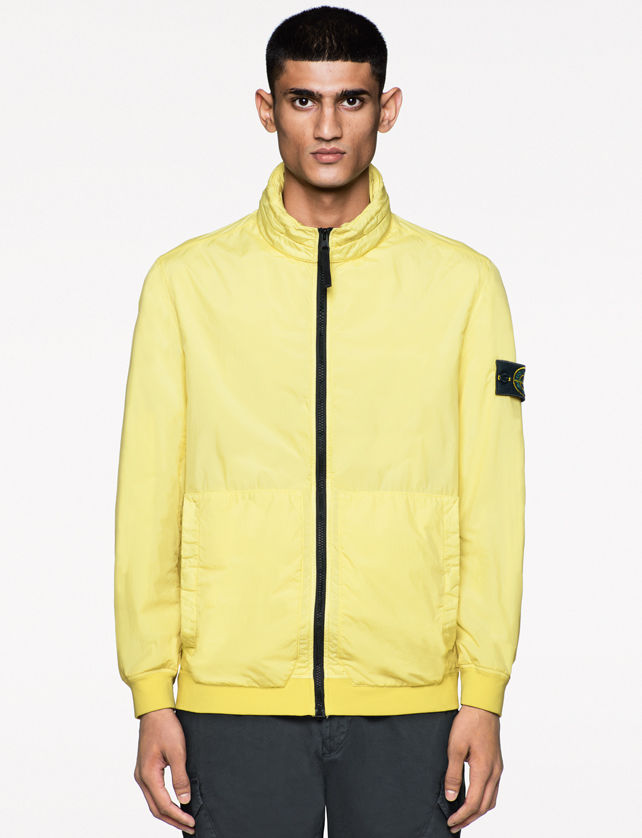 Model wearing a light yellow jacket with stand collar, black zipper closure and Stone Island badge on the left arm, darker yellow cuffs and waistband