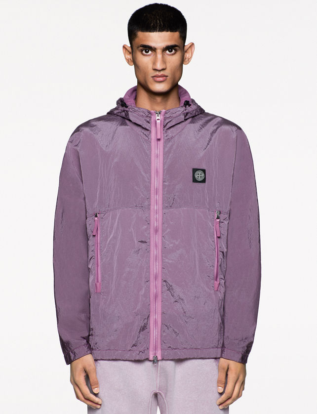 Model wearing a reflective light purple jacket with pink zipper closure and zippered side pockets, black logo patch on the chest