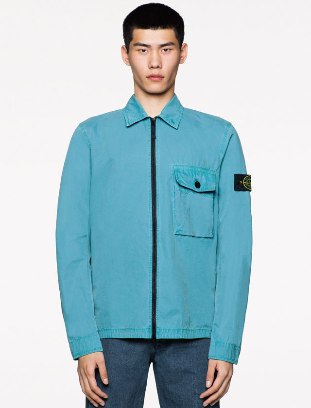 Model wearing a bright blue jacket with shirt collar, black zipper, a flap pocket on the chest with a black button, and Stone Island badge on the left sleeve