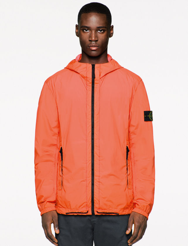 Model wearing a bright orange jacket with black zipper closure, side pockets, and Stone Island badge on the left sleeve