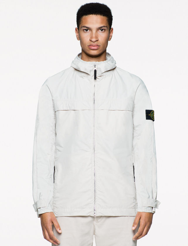 Model wearing a white zip up jacket with black zipper tab, high collar, and Stone Island badge on left arm