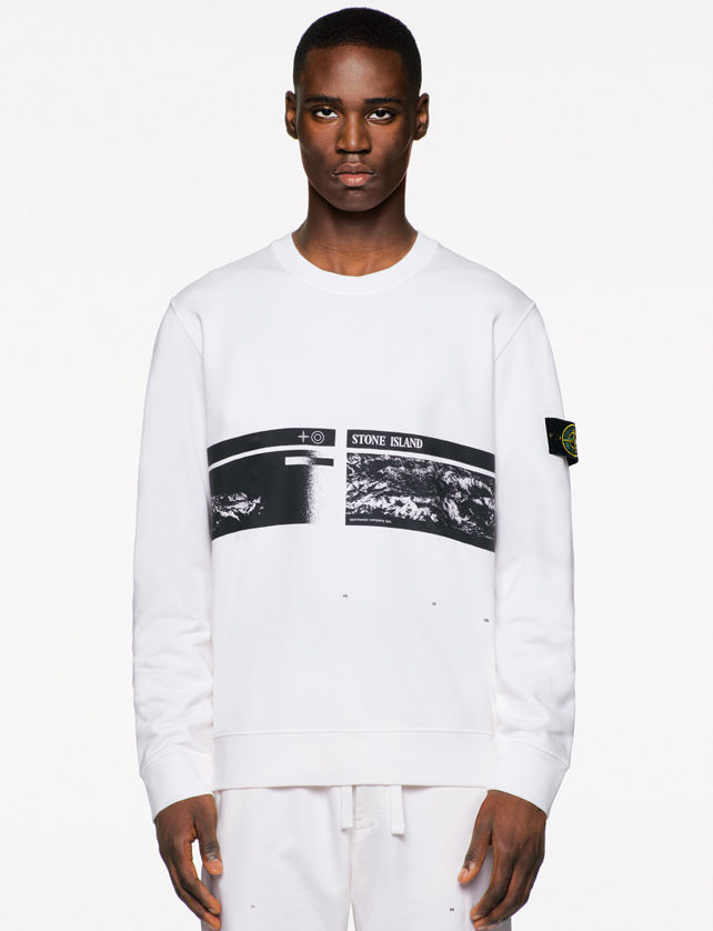 Model wearing a white sweatshirt with a Stone Island badge on the left sleeve and a black and white photo print on the chest featuring the Stone Island name and matching drawstring sweatpants