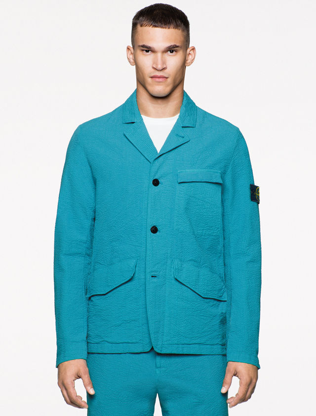 Model wearing a bright blue three button blazer jacket with notched lapels, chest pockets, two flap pockets on the front, and matching pants