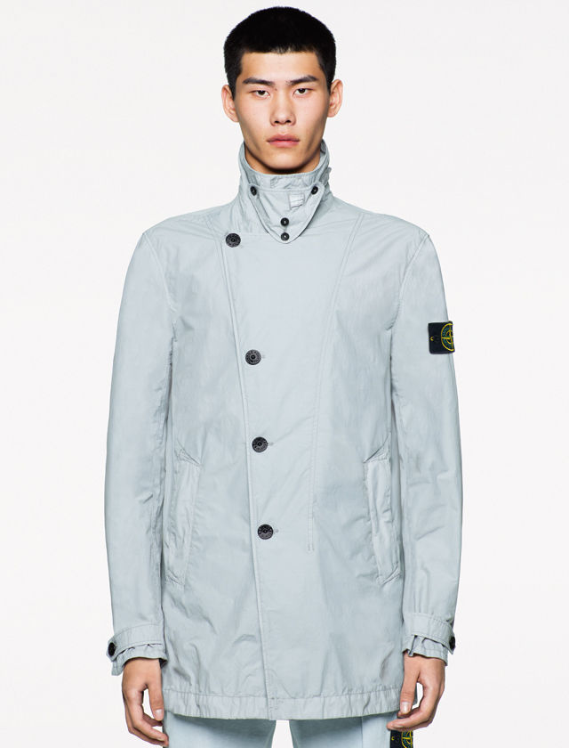 Model wearing a light gray jacket with an asymmetrical black button closure, buttoned high collar and buttoned cuffs, together with matching pants