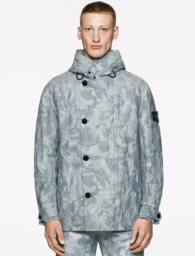 Model wearing a light blue and gray camouflage print jacket with a stand collar, asymmetrical black button closure, buttoned cuffs, together with matching pants