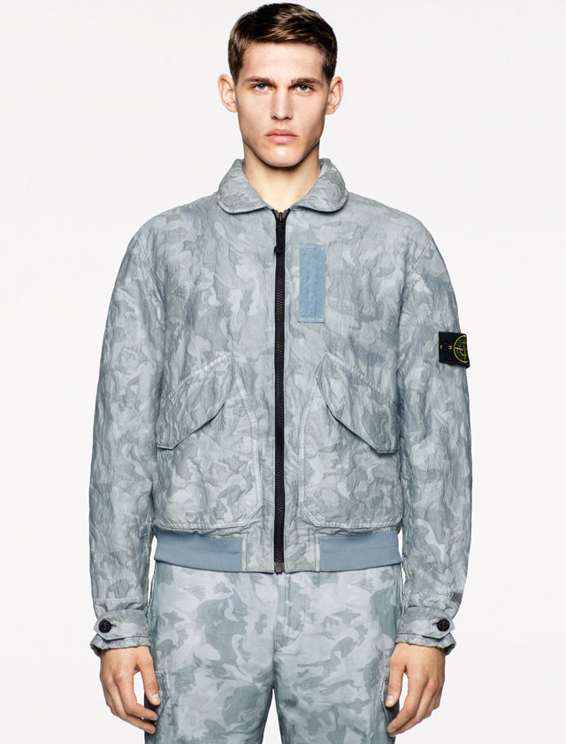 Model wearing a light blue camouflage print collared jacket with solid blue accents, Stone Island badge on the left arm, flap pockets on the chest, and matching pants