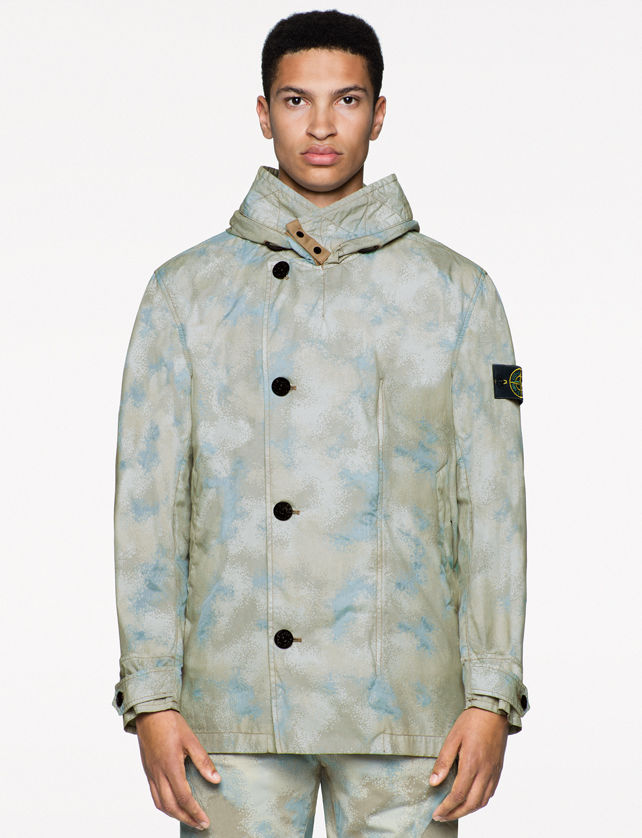 Model wearing a light blue and tan camouflage print jacket with a stand collar, asymmetrical black button closure, buttoned cuffs, together with matching pants