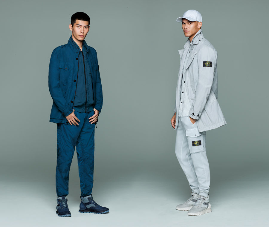 Two models in monochrome outfits, one wears a blue button up jacket over a matching zip up shirt and pants, the other wears a light gray cap, jacket with Stone Island badge on upper left sleeve, button down shirt, and cargo pants with Stone Island badge