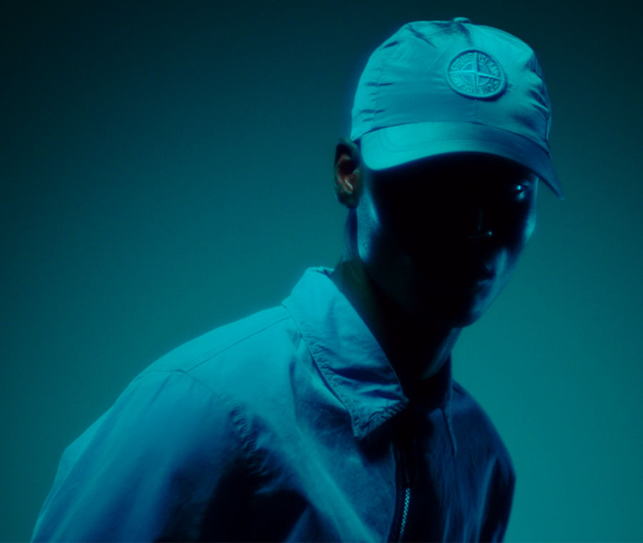 Model standing in shadow wearing a collared shirt jacket and a cap with the Stone Island compass rose.