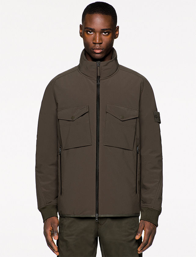 Model wearing dark brown jacket with zip up collar, black zipper closure, flap pockets on the chest and zippered side pockets.