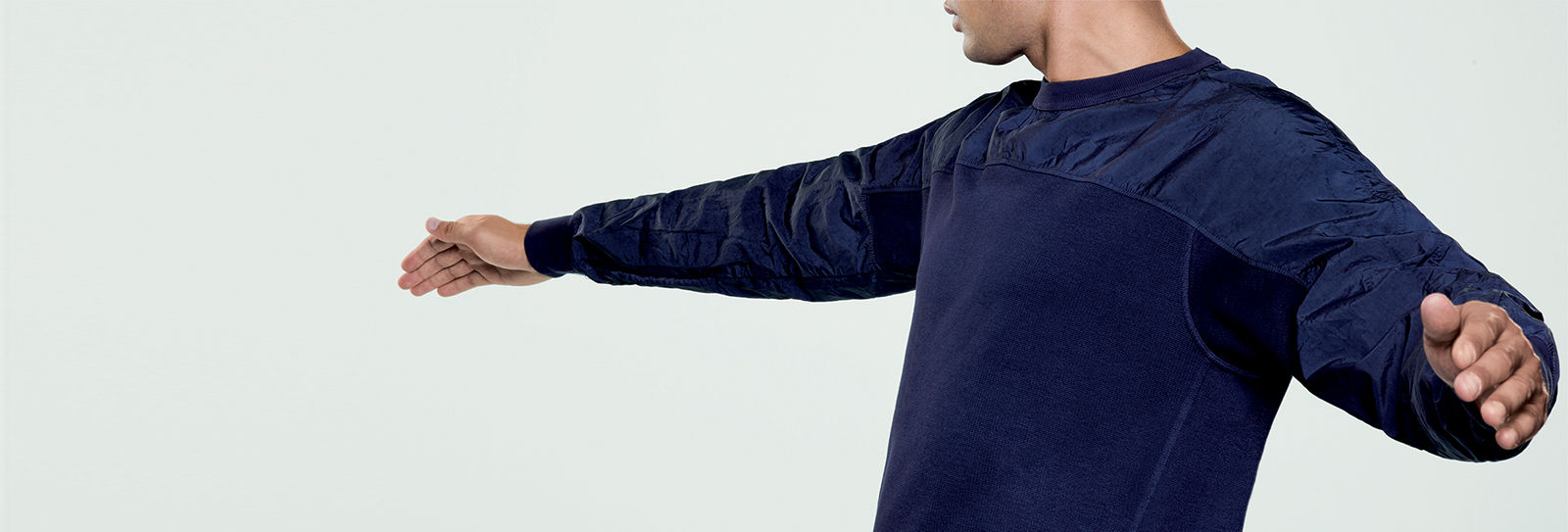 Model wearing navy blue sweatshirt in two different materials with ribbed cuffs and collar.