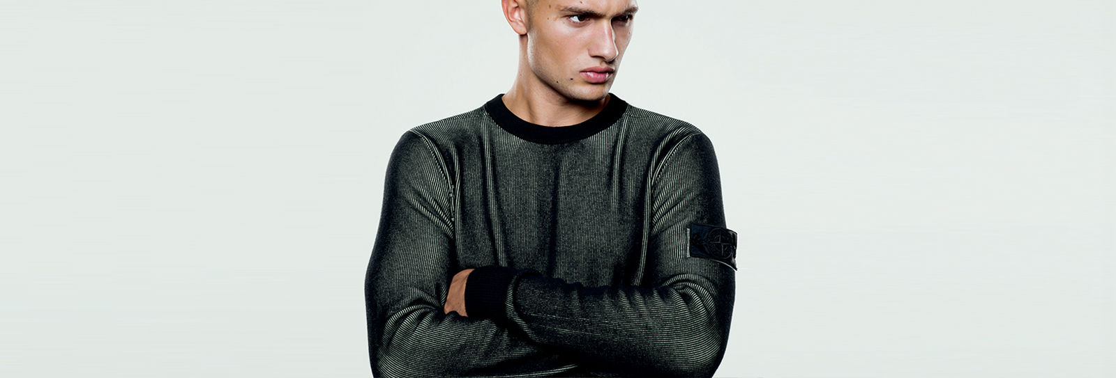 Model wearing dark colored crewneck sweater with the Stone Island Shadow badge on the upper left arm.