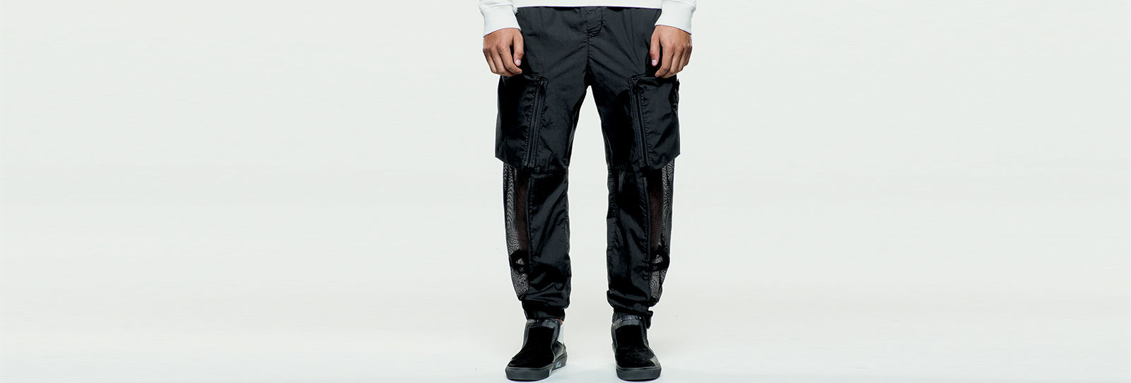 Model wearing black cargo pants with one large zippered pocket on each thigh and black slip on shoes.