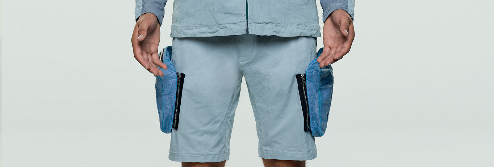 Model wearing light blue shorts with one large detachable pocket on each thigh in a different shade of blue, attached to the shorts with a black zipper.