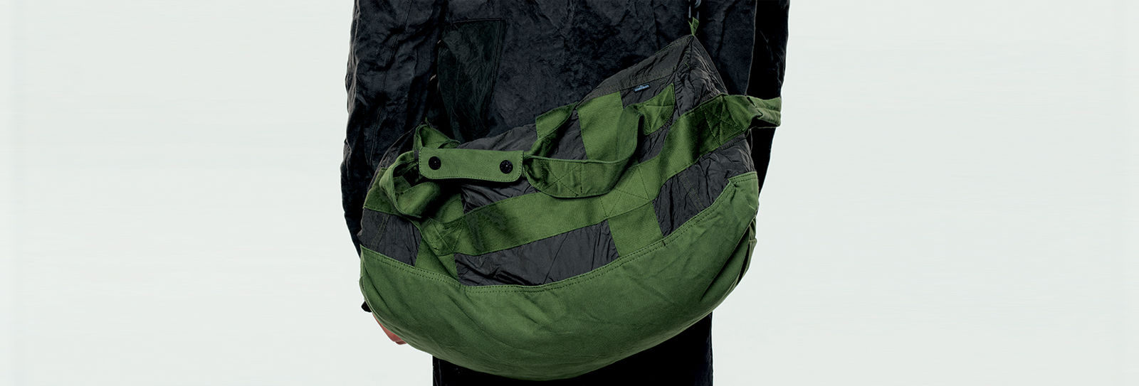Model carrying a dark green and black duffel bag with carry handles and shoulder strap.