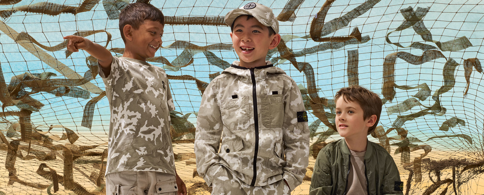 Three junior models, one wearing khaki cargo pants and a camouflage t shirt, another wearing a camouflage jacket with matching pants and cap, and the third wearing a khaki t shirt and military green bomber jacket.