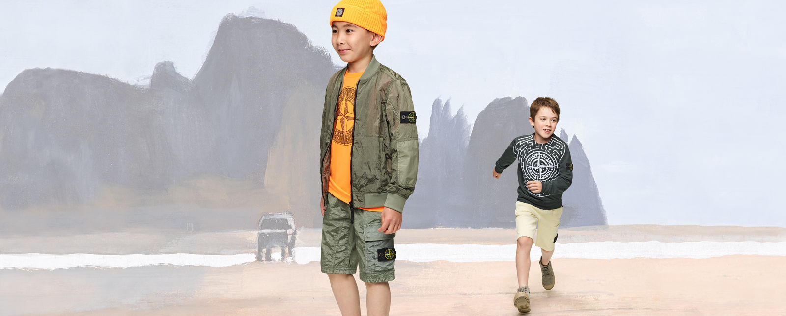 Two junior models, one wearing military green cargo shorts and jacket, a yellow top and beanie, the other one wearing cream shorts and a dark colored sweatshirt with the Stone compass rose across the chest.