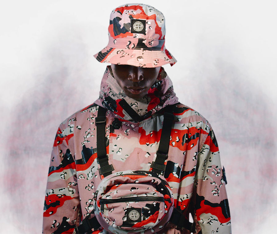 Model wearing a high collar jacket, a bucket hat and a chest pouch with black straps across the shoulders and waist, all in red, pink and off white camouflage print.