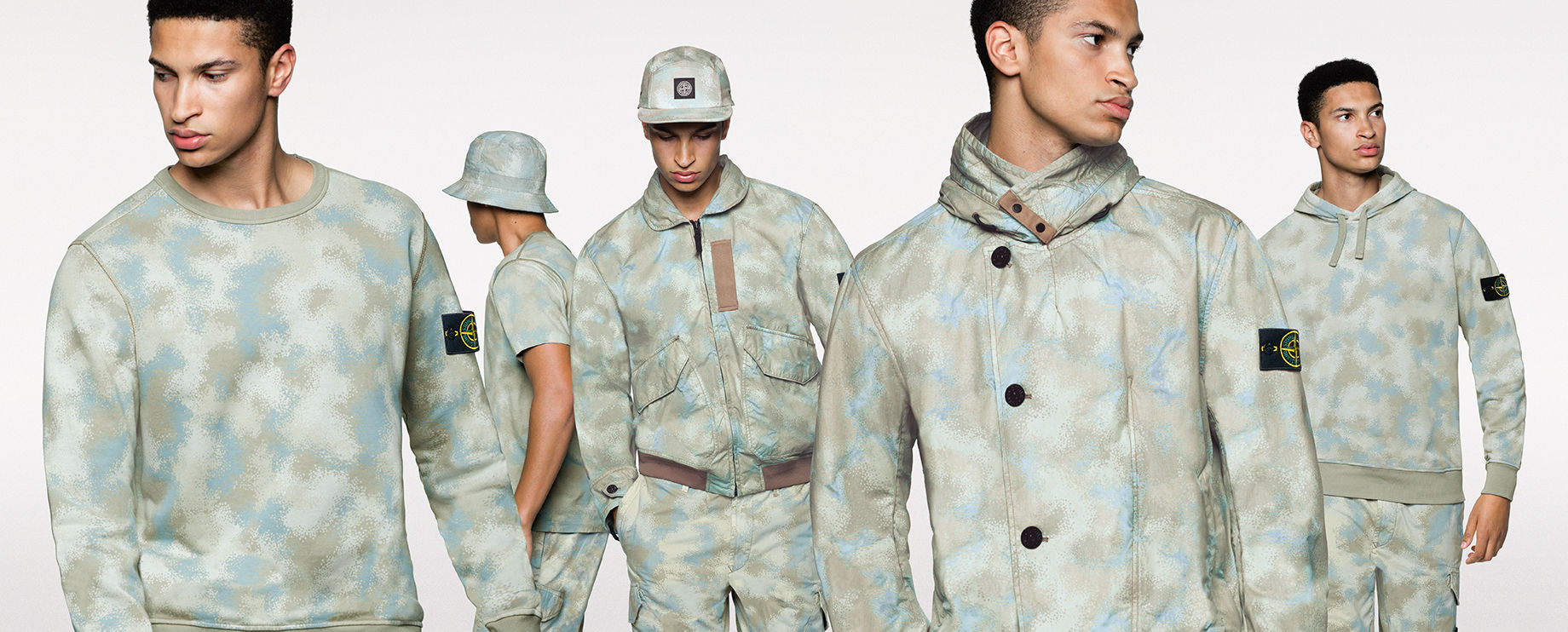 Five shots of the same model, showing the front and side view of him wearing different styles of sweatshirts, pants, shorts, jackets, hats and a t shirt, all in the same khaki and light blue camouflage print.