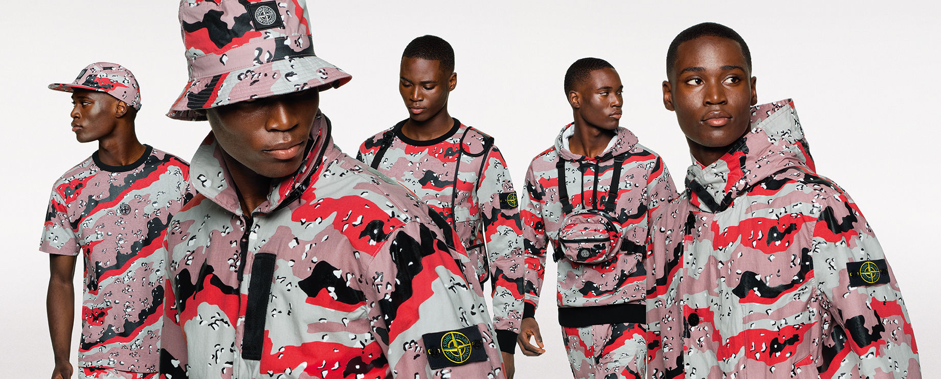 Five shots of the same model, wearing different styles of sweatshirts, pants, jackets, hats and a t shirt, all in the same pink, red and gray camouflage print.