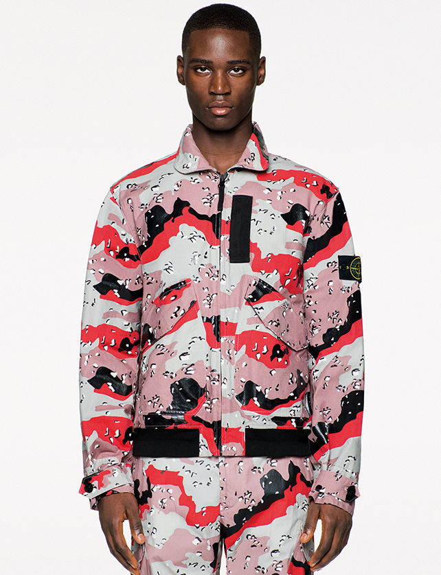 Model wearing a zip up collared jacket with flap pockets and an abstract red, pink, white, and black pattern together with matching pants