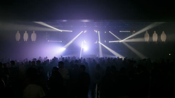 Crowd watching a stage with various spotlights shining down and banners with white silhouettes above it
