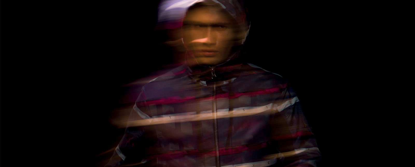 Blurred portrait of model wearing dark colored hooded jacket with white, black and red stripes and zipper closure.