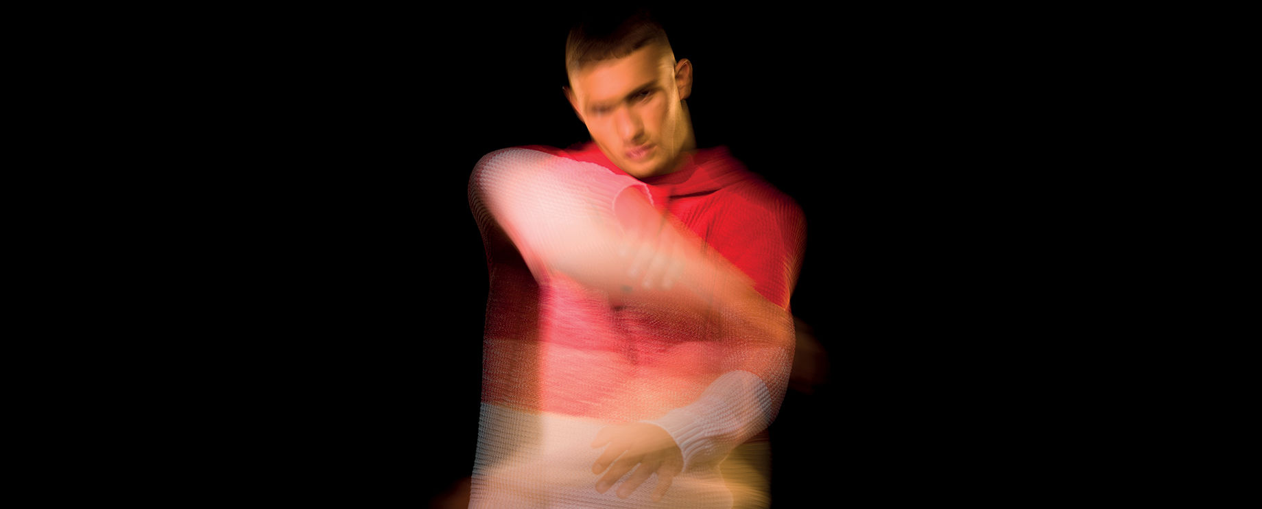 Blurred image of model wearing a sweater with red to white gradient stripes.