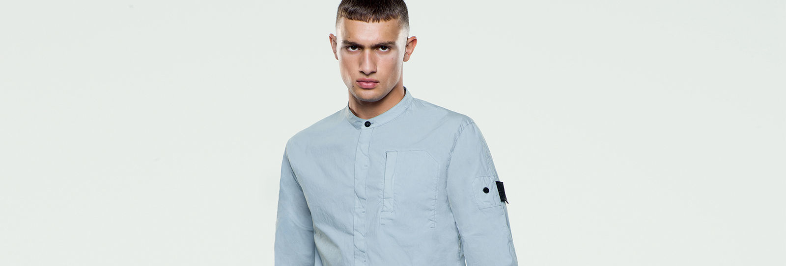 Model wearing long sleeved shirt with Mandarin collar with single button closure, concealed button placket and chest pocket on the left.