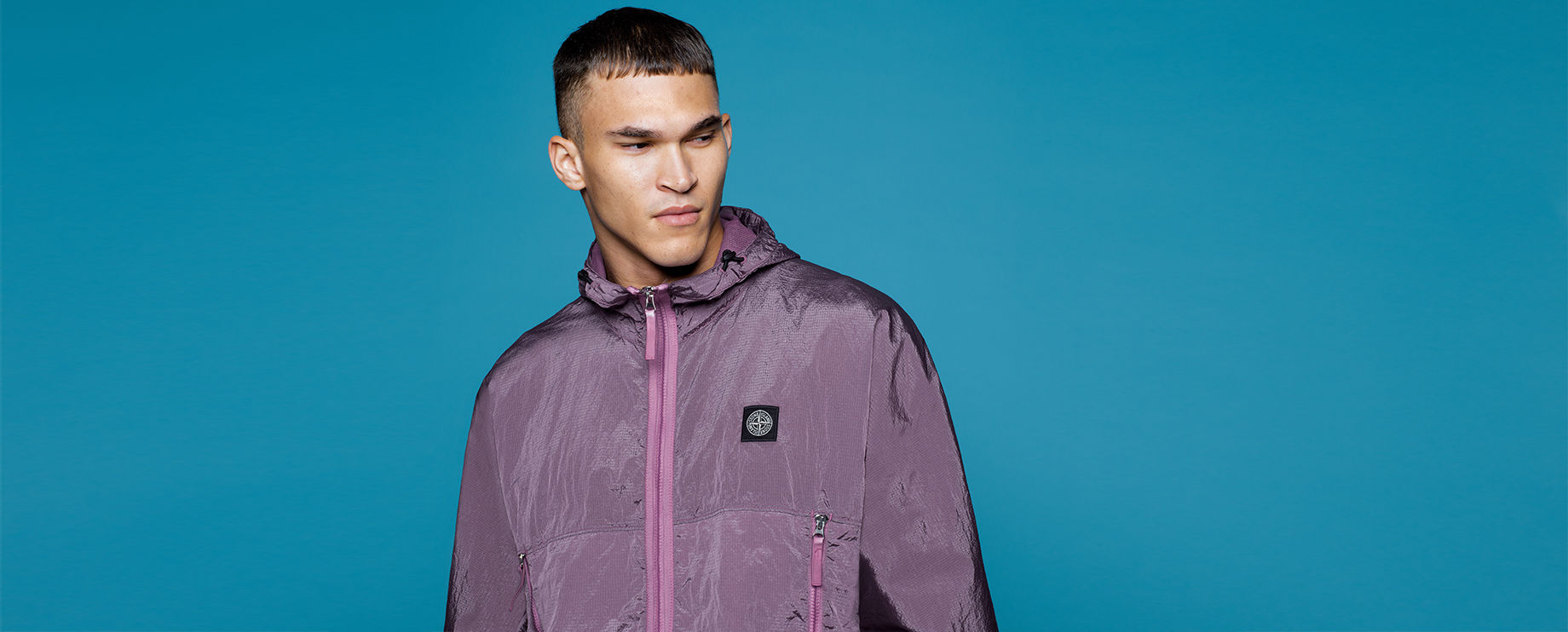 Model wearing a hooded purple jacket with high collar, zipper closure and Stone Island patch at left chest.